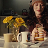 muccamukk: Darcy sitting at a table drinking coffee, flowers on her right. (Thor: Breakfast Table)