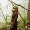 muccamukk: Telya standing in the forest. (SGA: Forest Woman)