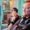aqua_eyes: John staring at Rodney (sucking on something?) with a turquoise and orange Atlantis in background (SGA - McShep - McShep)
