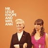 metatxt: leslie knope dressed in suit, accompanied by ladyfriend ann, who wears a pink party dress (parks: mr leslie + wife ann)