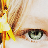 songbird: closeup of a green eye with blond hair and a yellow flower framing (eye)