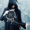 sylvaine: Woman in a dark hooded cloak holding a dreamcatcher. ([gen] Pagan - into dreams)