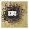 forthwritten: white cassette tape lying on tangled magnetic tape (tape)