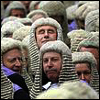 gramarye1971: smiling UK justice amongst a sea of other justices wearing court wigs (Wig in a Box)