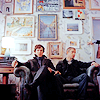 jenwryn: John and Sherlock against the wall covered in frames and pictures. (sherlock • john/sherlock; painting'd wal)