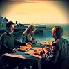 pipisafoat: john, teyla, and rodney (tv: stargate atlantis) eating at a table together. it loos like the sun is setting (ar1)