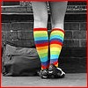 mousme: A view of a woman's legs from behind, wearing knee-high rainbow socks. The rest of the picture is black and white. (Postmodern)