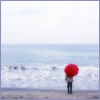 elizabeth: figure with a red umbrella beside a stormy sea (small)