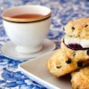 oulfis: A teacup next to a plate of scones with clotted cream and preserves. (teacup)