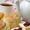 oulfis: A teacup and teapot next to a pile of scones, some with clotted cream and preserves. (teapot, calm, tea, british, scones, happy)