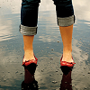 inland_territory: woman's legs, standing on a beach, with rolled up blue-jeans and red shoes on (default)
