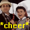 were_lemur: Seventh Doctor (white male) and Ace (white female) looking happy, text *cheer* (7th Doctor and Ace cheering)