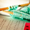 indeliblesasha: Blue/teal yarn on straight knitting needles, resting on a book (Knitting - Blue yarn)