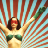 ext_53028: Superheroine with arms lifted to the sky like antennas, big green gloves. (I got the power)