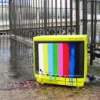 analoguechild: picture of a tv outside on the cement infront of a iron fence showing the color test screen. (tv or movie rambledansen)