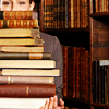 esther_asphodel: a woman with her face almost concealed by stack of books (bibliophile)