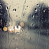 the_coffee_shop: Rain splattered on a window, with blurry lights off in the distance. (kayne)