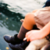 fascination: Someone sitting by the water wearing a skirt and black boots. (By the water.)