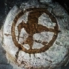 nightmachinery: A rough flattened bread with a floured top, save a darkened area of the crust in the Mockingjay symbol. (Baker - Mockingbread)
