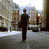 ar: Evey Hammond in V for Vendetta (film) walks away from the camera on a road in London. (vfv - the city at sunrise)