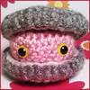 dorinda: A little clam made of pink and grey yarn, peeking out of its shell with googly eyes. (clam_cute)