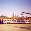 """frangipani: a crowd of people holding a banner that says, """"every war has an end"""" (a stranger's love)"""