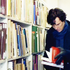 fastidious: Sherlock avidly looking up things in books. Shelves of books in background. (Sherlock - Library)