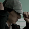 fastidious: Screenshot from the tv show Sherlock. It is a profile shot with him adjusting a deerstalker-type hat. (Sherlock - Hat Man)