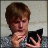 msilverstar: Bradley James as Arthur (offscreen, using a PDA) (mythacronism)