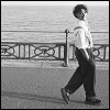 cranky_x_crocus: Grinning woman, short-cropped curly hair, suit and shirt, trouser braces; strutting on pavement in front of an ocean. (Women || Zoë Lewis strutting.)