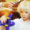 lysergia: small frowning blonde boy playing with a toy airplane (come home)