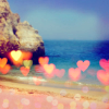 revolutions: A photograph of a beach, with little hearts scattered across the picture. (the sea is love)