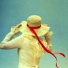feather_ghyll: Back of girl whose gloved hand is holding on to her hat. (Girl in a hat)