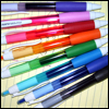 ficdaily: A 'fan' of pens in a rainbow of colours spread out on a yellow pad of paper. (Default)