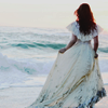 anaraine: A woman in a white dress with tattered edges stands at the edge of the ocean. ([photo] waves upon her feet)