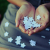 ember: Photo of cupped hands holding cut-out paper stars. (hopeful, magical, paper stars, whimsical)