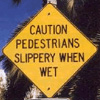 "sineala: A road sign that reads ""CAUTION PEDESTRIANS SLIPPERY WHEN WET"" (slippery)"
