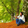 genarti: woman curled up with book, under a tree on a wooded slope in early autumn ([misc] perfect moments)