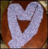 jumpuphigh: Purple scarf on table shaped like a heart. (Knit heart)