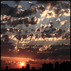 sporky_rat: A setting sun cloudscape with sunrays through broken clouds (gonna explode into millions of sky dust)
