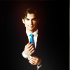 neekabe: Neal Caffrey adjusting his cuff-links. He's wearing a black suit against a black background.  (Default)