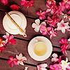 hohaiyee: Tea that's yellow like butter within its cup, upon a maroon hued table, strewn with hot pink flowers shaped like stars (Bloom)