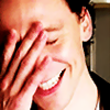 actiaslunaris: Tom Hiddleston - grinning, eyes shut, hand on his face (*facepalm*)