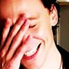 actiaslunaris: Tom Hiddleston - grinning, eyes shut, hand on his face (*facepalm*)