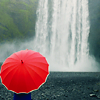 elizabeth: someone holding a red umbrella, facing a waterfall (strength)