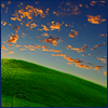 auburn: Tangerine clouds on dark blue sky over green hill (Fiery Clouds)