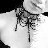 169: black-and-white picture of a young woman wearing a black beaded necklace (necklaces)