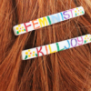 aphrodite_mine: barrettes in reddish hair read 'feminist killjoy' (new girl - grin?)