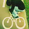 forthwritten: a bike painted on the ground to indicate a cycling path and a person lying on the ground pretending to ride it (cyclist)