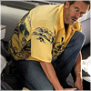 highlander_ii: House wearing a yellow tropical shirt kneeling over a patient ([House] kneeling - yellow shirt)